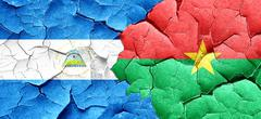 nicaragua flag with Burkina Faso flag on a grunge cracked wall - stock illustration