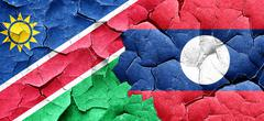 Namibia flag with Laos flag on a grunge cracked wall - stock illustration