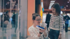 Mother shows daughter a gift box just baught at mall. Being excited about Stock Footage