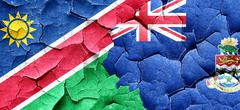 Namibia flag with Cayman islands flag on a grunge cracked wall Stock Illustration