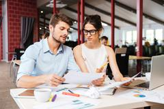 Serious young business man and woman working together in office Stock Photos