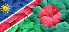 Namibia flag with Bangladesh flag on a grunge cracked wall - stock illustration