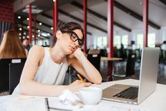 Bored businesswoman working using laptop in office - stock photo