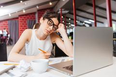 Tired business woman sitting and working with laptop in office - stock photo