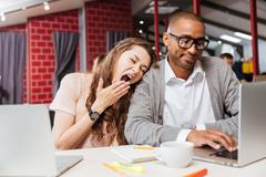 Tired bored business people yawning and working with laptop - stock photo