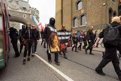 LONDON - ENGLAND 1ST MAY 2016 - An anarchist group with a slogan and masks mo - stock photo