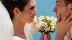 married hugging on a background the sea with a wedding bouquet - stock footage
