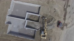 4k aerial high hoe shovel drops sand into foundation - stock footage