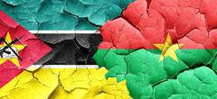 Mozambique flag with Burkina Faso flag on a grunge cracked wall - stock illustration