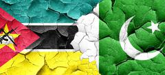 Mozambique flag with Pakistan flag on a grunge cracked wall - stock illustration