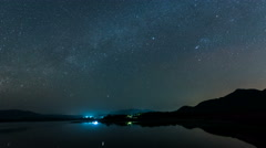 Time lapse-shooting star and milky way over reservoir with mountain night sky Stock Footage
