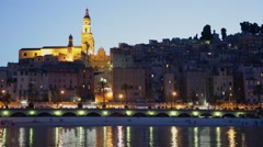 Menton town in the night with light reflections in the sea - stock footage