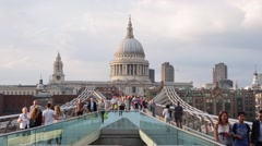 Millennium bridge with people walking and St Paul cathedral in London - stock footage