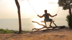 The guy with tattoo on his shoulder going on the swings at the seaside - stock footage