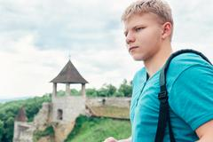 Young man tourist on the old castle territory Stock Photos
