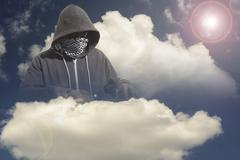 Hooded and masked computer hacker thief with a cloud computer based backgroun - stock photo