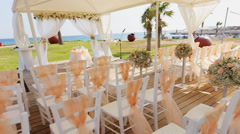 Chairs at a wedding tent by the sea Stock Footage