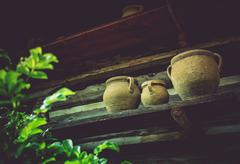 Vintage Earthenware on a Shelf Outside of Old Log Cabin. Aged Ceramic Crocks. Stock Photos