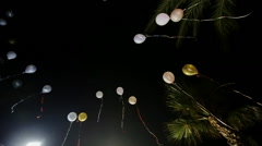 balloons rising into the night sky - stock footage