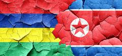 Mauritius flag with North Korea flag on a grunge cracked wall Stock Illustration