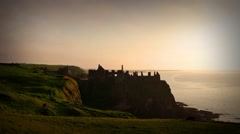 Dunluce Castle in warm evening light during sunset, Northern Ireland Stock Footage