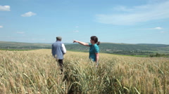 Farmer and business partner talking about business, making plans in wheat field  Stock Footage