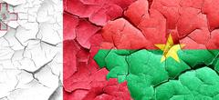 Malta flag with Burkina Faso flag on a grunge cracked wall - stock illustration