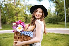 Smiling woman holding basket with flowers, drinks and food - stock photo