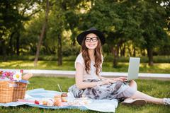 Smiling pretty young woman using laptop on picnic in park Stock Photos