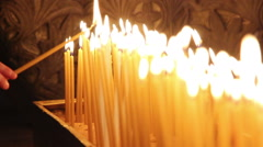 A row of burning church candles with a changing focus Stock Footage