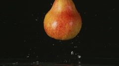 SLOW: A splash - A red pear falls on a black background Stock Footage