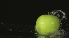 SLOW: A water flow falls on a green apple on a black background - stock footage