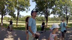 Father, mother daughter and son walk on sidewalk in park Stock Footage