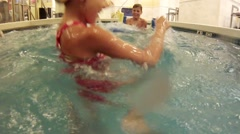 Happy girl and boy fight in indoor pool, action camera Stock Footage
