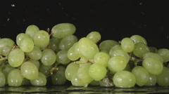 SLOW: A splash - A green grape bunch falls on a black background - stock footage
