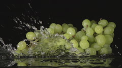 SLOW: A water flow falls on a bunch of grape on a black background - stock footage