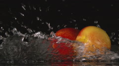 SLOW: A water flow falls on a nectarines on a black background Stock Footage