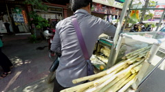 Vendor preparing raw sugar cane juice in the morning. Stock Footage