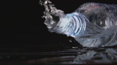 SLOW: A plastic bottle falls on a black table and water pours from it Stock Footage