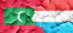 Maldives flag with Luxembourg flag on a grunge cracked wall Stock Illustration