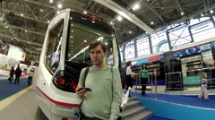 Man (with model release) near modern tram at exhibition ExpoCityTrans Stock Footage