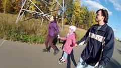 Happy man, woman and girl roller skate on road Stock Footage