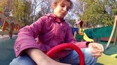 Girl on seesaw on playground at fall day, action camera Stock Footage
