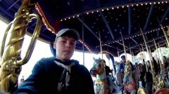 Boy makes selfie on carousel attraction in Disneyland Stock Footage