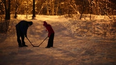 Girl with her father start to play hockey with ball in winter evening Stock Footage