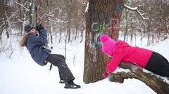 Boy riding on bungee in winter snowy forest and girl catches he Stock Footage