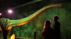 Boy and girl look at dinosaur at Show of dinosaurs in pavillion of VDNKH Stock Footage