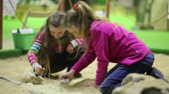 Two girls with brushes dig into sand dinosaur bones together Stock Footage