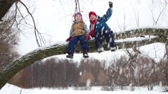 Two boys sit on thick branch, wave hands and snow falls in winter day Stock Footage