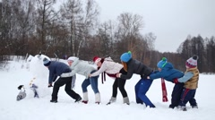 Six people play - try to raise snowman at winter day Stock Footage